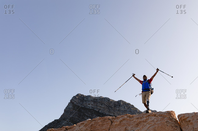 Fit, disabled mixed race male athlete with prosthetic leg, enjoying his time on a trip to the mountains, hiking on the rocks with his arms above his head with sticks. Active lifestyle with disability.
