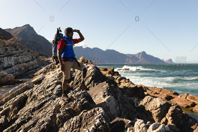 A fit, disabled mixed race male athlete with prosthetic leg, enjoying his time on a trip to the mountains, hiking, admiring the view of the sea. Active lifestyle with disability.