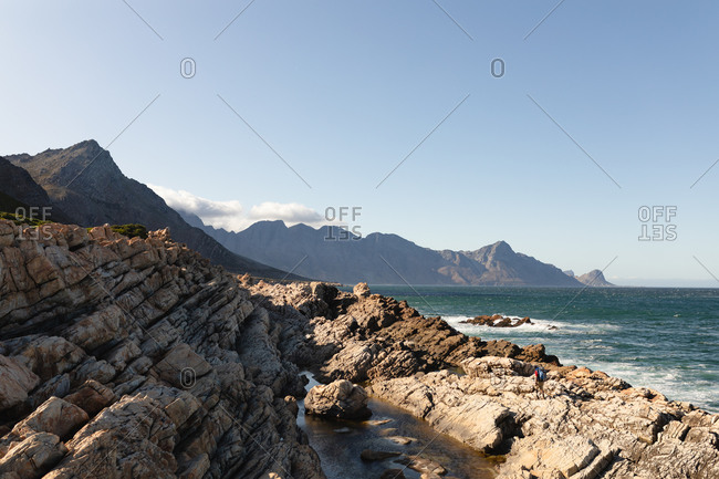 Rocky coastal cliffs by a calm, blue sea with clear blue sky on a sunny day. Beautiful natural scenery by the coast.
