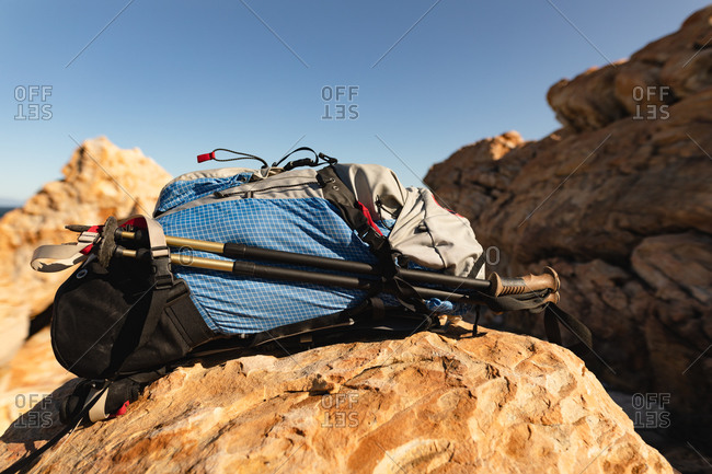 A hiker's backpack and Nordic walking sticks sitting on a rock on rocky coastal cliffs with clear, blue sky on a sunny day. Beautiful natural scenery by the coast.
