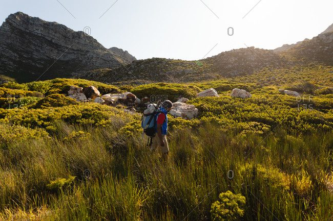 A fit, disabled mixed race male athlete with prosthetic leg, enjoying his time on a trip to the mountains, hiking, walking through grass. Active lifestyle with disability.