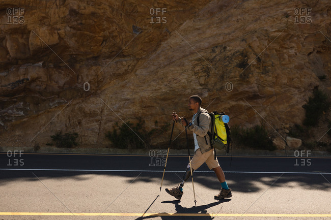 A fit, disabled mixed race male athlete with prosthetic leg, enjoying his time on a trip to the mountains, hiking with sticks, walking on the road in the mountains. Active lifestyle with disability.
