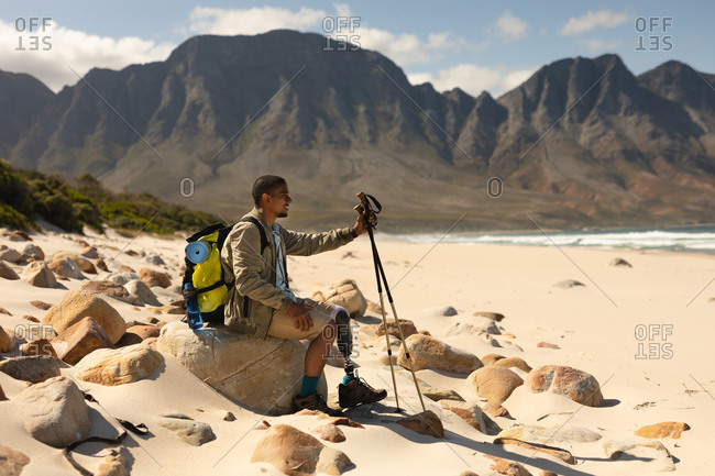 A fit, disabled mixed race male athlete with prosthetic leg, enjoying his time on a trip to the mountains, hiking with sticks, resting on the beach. Active lifestyle with disability.
