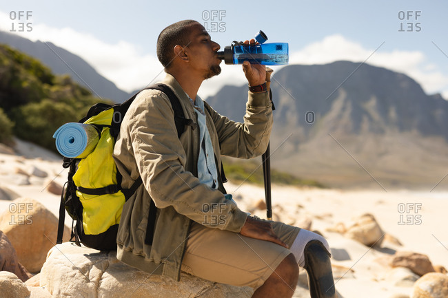 A fit, disabled mixed race male athlete with prosthetic leg, enjoying his time on a trip to the mountains, hiking with sticks, drinking water on the beach, resting. Active lifestyle with disability.