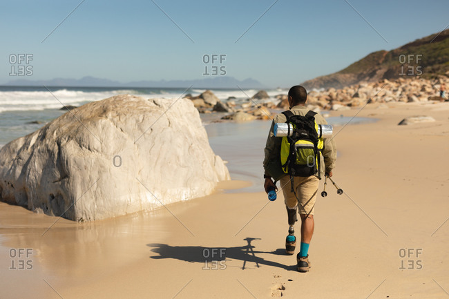 A fit, disabled mixed race male athlete with prosthetic leg, enjoying his time on a trip to the mountains, hiking with sticks, walking on the beach by the sea. Active lifestyle with disability.