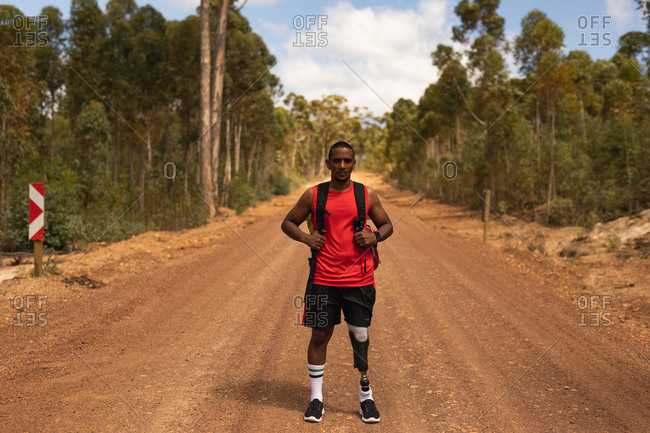 A portrait of a fit, disabled mixed race male athlete with prosthetic leg, enjoying his time on a trip, hiking, standing on dirt road in a forest. Active lifestyle with disability.