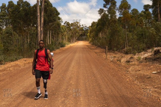 A fit, disabled mixed race male athlete with prosthetic leg, enjoying his time on a trip, hiking, walking on dirt road in a forest. Active lifestyle with disability.