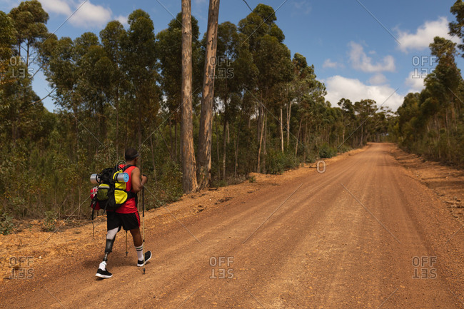 A fit, disabled mixed race male athlete with prosthetic leg, enjoying his time on a trip, hiking, walking with sticks on dirt road in a forest. Active lifestyle with disability.
