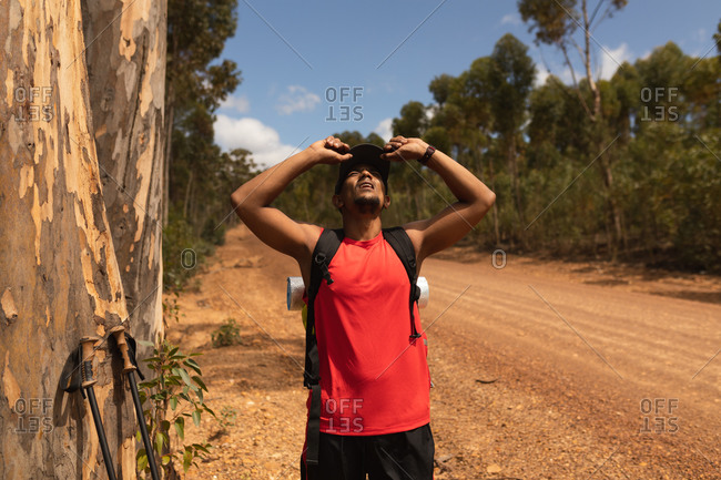 A fit, disabled mixed race male athlete with prosthetic leg, enjoying his time on a trip, hiking, standing on a dirt road in a forest, taking a break. Active lifestyle with disability.
