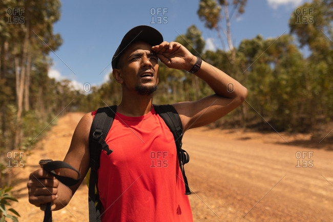 A fit, disabled mixed race male athlete with prosthetic leg, enjoying his time on a trip, hiking, standing on a dirt road in a forest, looking ahead. Active lifestyle with disability.