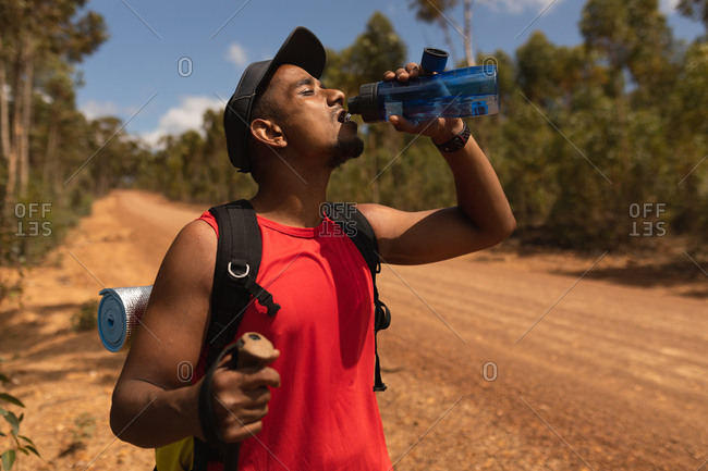 A fit, disabled mixed race male athlete with prosthetic leg, enjoying his time on a trip, hiking, standing on a dirt road in a forest, drinking water. Active lifestyle with disability.