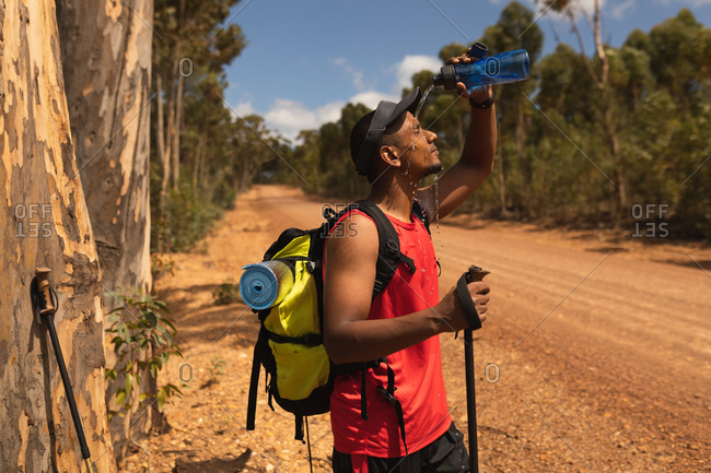 A fit, disabled mixed race male athlete with prosthetic leg, enjoying his time on a trip, hiking, standing on a dirt road in a forest, pouring water on himself. Active lifestyle with disability.