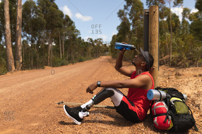 A fit, disabled mixed race male athlete with prosthetic leg, enjoying his time on a trip, hiking, sitting on a dirt road in a forest, pouring water on himself. Active lifestyle with disability.
