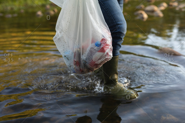 Low section of conservation volunteer cleaning up river in the countryside, carrying bag full of rubbish. Ecology and social responsibility in rural environment.