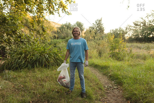 Portrait of happy Caucasian male conservation volunteer cleaning up forest in the countryside, holding rubbish bag, smiling to camera. Ecology and social responsibility in rural environment.