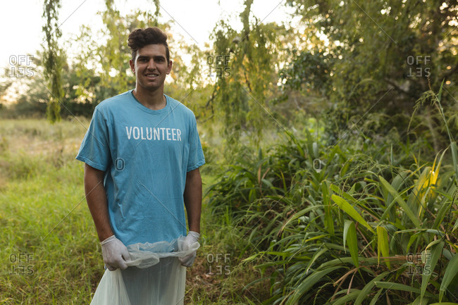 Portrait of happy mixed race male conservation volunteer cleaning up forest in the countryside, holding rubbish bag, smiling to camera. Ecology and social responsibility in rural environment.