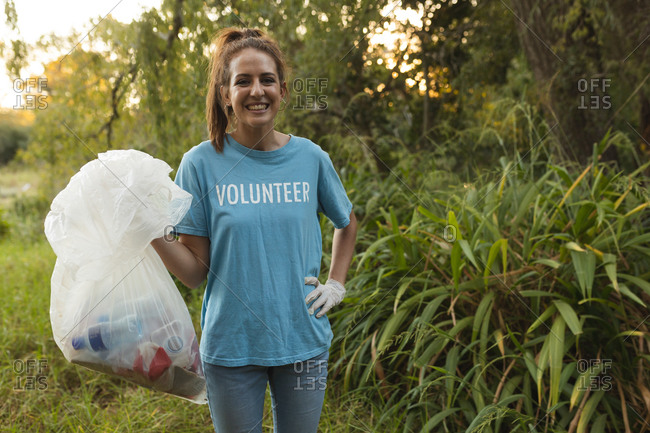 Portrait of happy Caucasian female conservation volunteer cleaning up forest in the countryside, holding rubbish bag, smiling to camera. Ecology and social responsibility in rural environment.