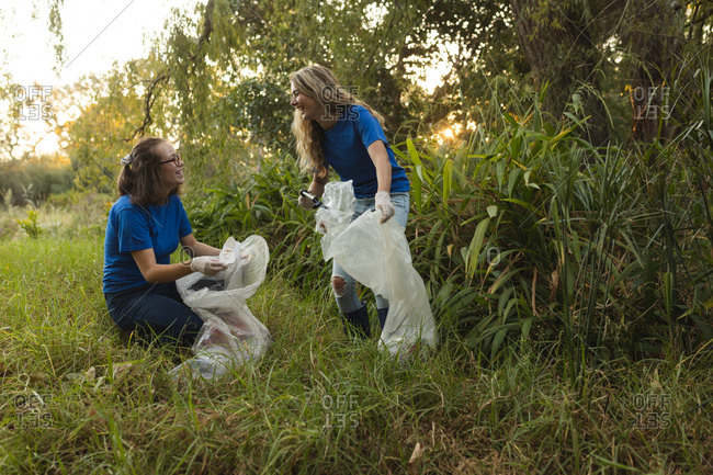 Two Caucasian female conservation volunteers cleaning up forest in the countryside, picking up rubbish. Ecology and social responsibility in rural environment.
