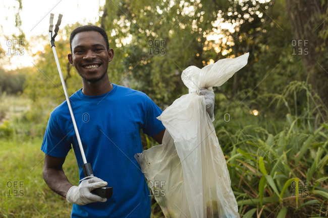 Portrait of African American male conservation volunteer cleaning up forest in the countryside, smiling holding rubbish bag and grabber. Ecology and social responsibility in rural environment.
