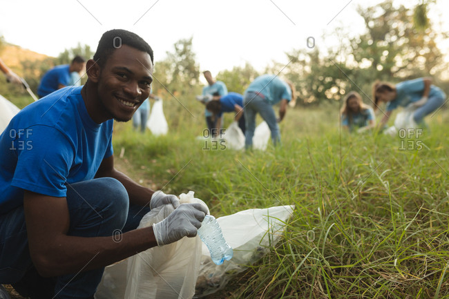 Portrait of African American male conservation volunteer cleaning up forest in the countryside, smiling to camera holding rubbish bag. Ecology and social responsibility in rural environment.