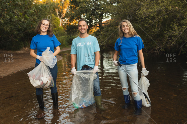 Three Caucasian male and female conservation volunteers cleaning up river in the countryside, holding rubbish bags and grabber. Ecology and social responsibility in rural environment.
