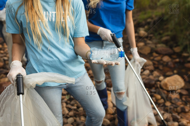 Mid section of two female conservation volunteers cleaning up river in the countryside, picking up rubbish holding plastic bottle, refuse sacks. Ecology and social responsibility in rural environment.