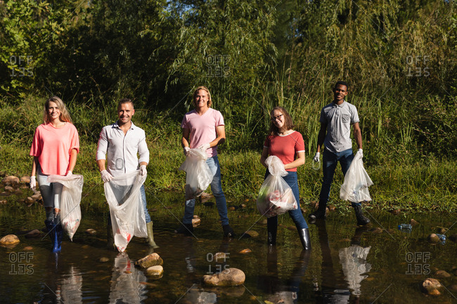 Portrait of multi ethnic group of conservation volunteers cleaning up river in the countryside, holding rubbish bags. Ecology and social responsibility in rural environment.