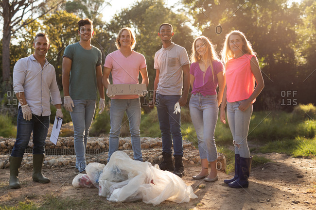 Portrait of multi ethnic group of happy conservation volunteers cleaning up river in the countryside with board Our Earth and bags with rubbish. Ecology and social responsibility in rural environment.