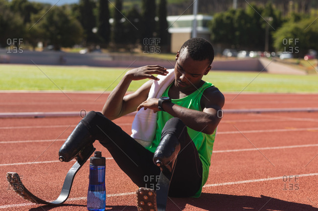 Fit, mixed race disabled male athlete at an outdoor sports stadium, sitting on race track after race checking his smartwatch with water bottle wearing running blades. Disability athletics sport
