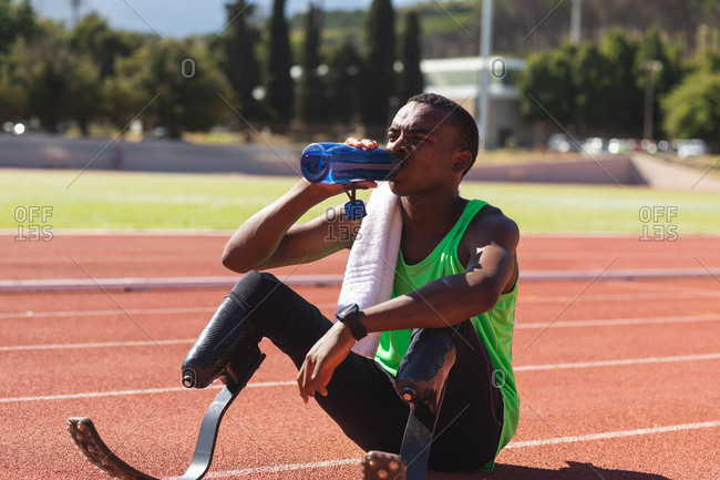 Fit, mixed race disabled male athlete at an outdoor sports stadium, sitting on race track after race drinking water wearing running blades. Disability athletics sport training.