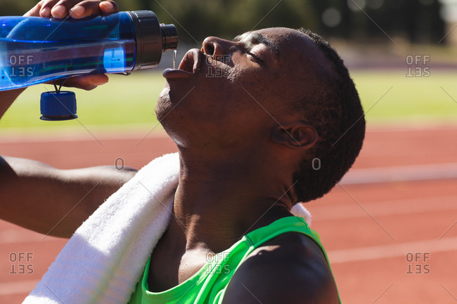 Fit, mixed race male athlete at an outdoor sports stadium, sitting on race track after race drinking water with towel on his shoulder. Athletics sport training.
