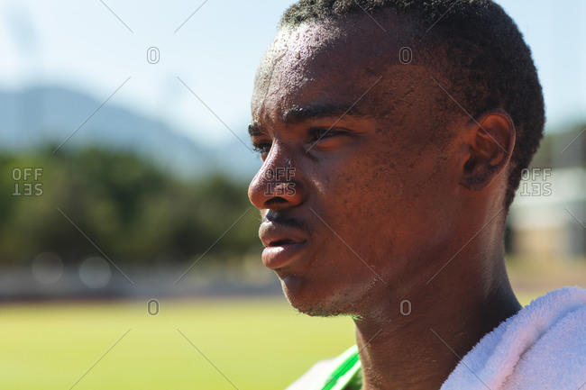 Close up of fit, focused mixed race male athlete at an outdoor sports stadium, on race track after race with towel on his shoulder. Athletics sport training.