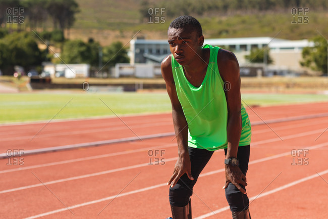 Fit, mixed race disabled male athlete at an outdoor sports stadium, on race track after race breathing and resting wearing running blades. Disability athletics sport training.