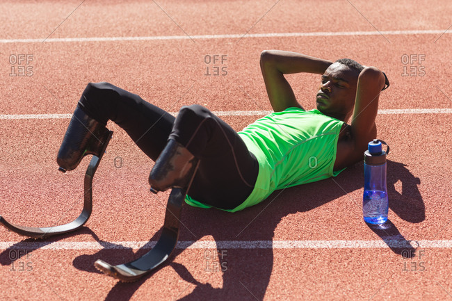 Fit, mixed race disabled male athlete at an outdoor sports stadium, lying on race track after race with water bottle wearing running blades. Disability athletics sport training.