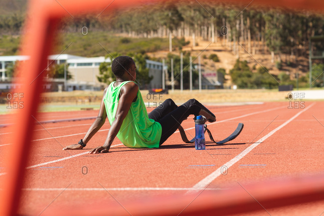 Fit, mixed race disabled male athlete at an outdoor sports stadium, sitting on race track after race with water bottle wearing running blades. Disability athletics sport training.
