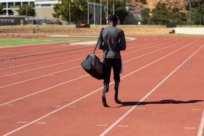 Rear view of fit, mixed race disabled male athlete at an outdoor sports stadium, walking with gym bag on race track wearing running blades. Disability athletics sport training.