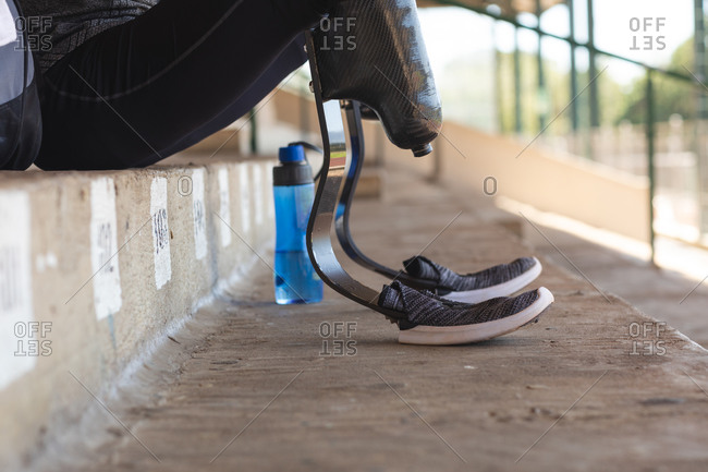 Low section of fit, mixed race disabled male athlete at an outdoor sports stadium, sitting in the stands wearing running blades. Disability athletics sport training.