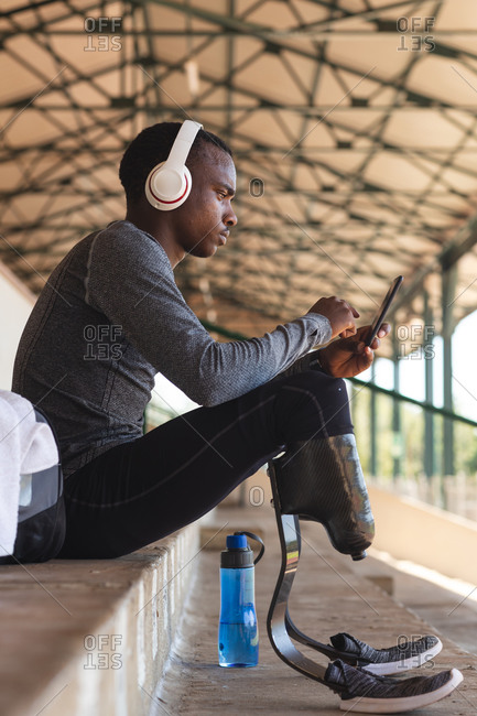 Fit, mixed race disabled male athlete at an outdoor sports stadium, sitting in the stands wearing headphones using smartphone wearing running blades. Disability athletics sport training.