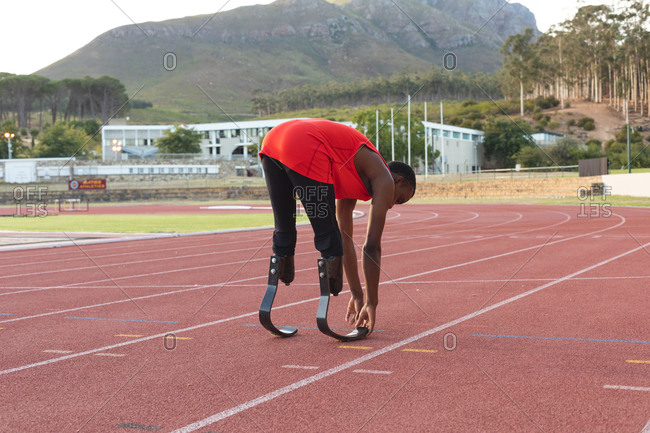 Fit, mixed race disabled male athlete at an outdoor sports stadium, on race track warming up before a race stretching wearing running blades. Disability athletics sport training.