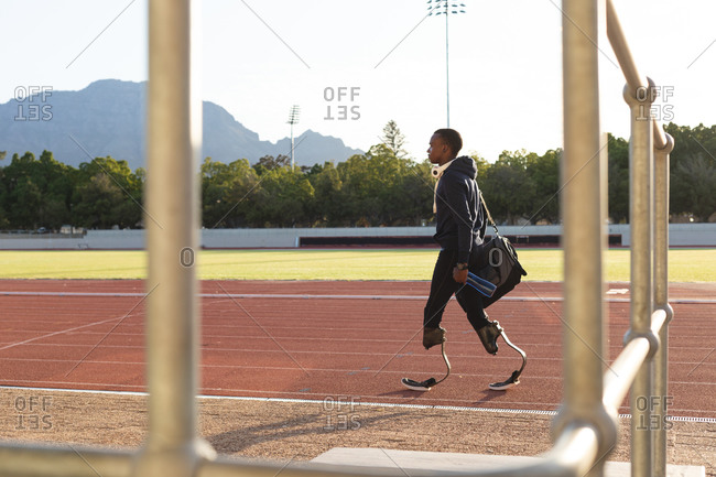 Fit, mixed race disabled male athlete at an outdoor sports stadium, walking with gym bag and water bottle on race track wearing running blades. Disability athletics sport training.