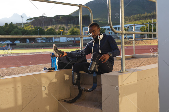 Fit, mixed race disabled male athlete at an outdoor sports stadium, sitting by race track preparing holding sports shoe wearing running blades. Disability athletics sport training.