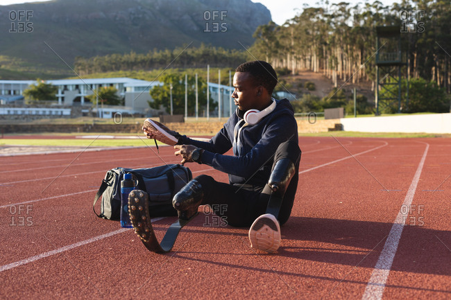 Fit, mixed race disabled male athlete at an outdoor sports stadium, sitting preparing holding sports shoe on race track wearing running blades. Disability athletics sport training.