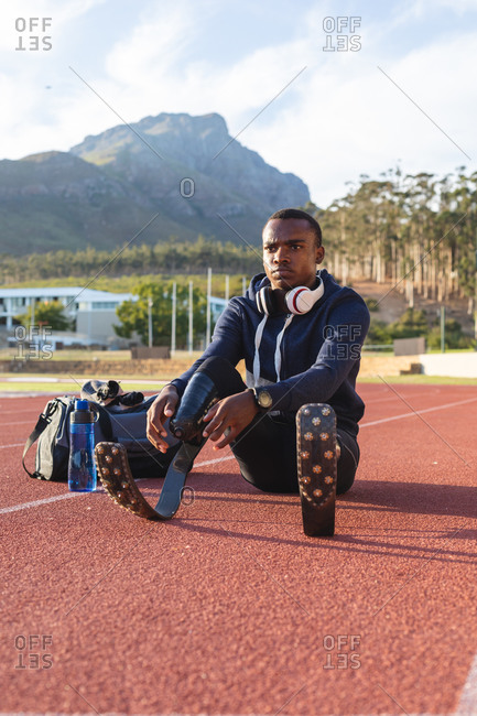 Fit, mixed race disabled male athlete at an outdoor sports stadium, with gym bag and water bottle preparing on race track wearing running blades. Disability athletics sport training.