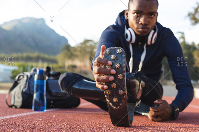 Fit, mixed race disabled male athlete at an outdoor sports stadium, with gym bag and water bottle stretching on race track wearing running blades. Disability athletics sport training.