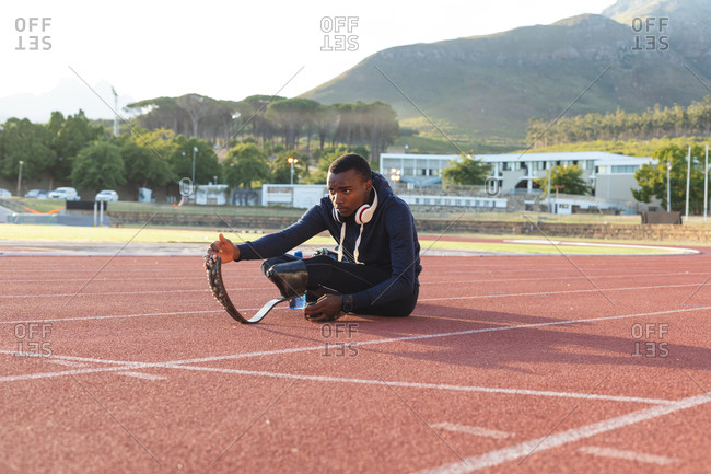 Fit, mixed race disabled male athlete at an outdoor sports stadium, warming up stretching on race track wearing running blades. Disability athletics sport training.