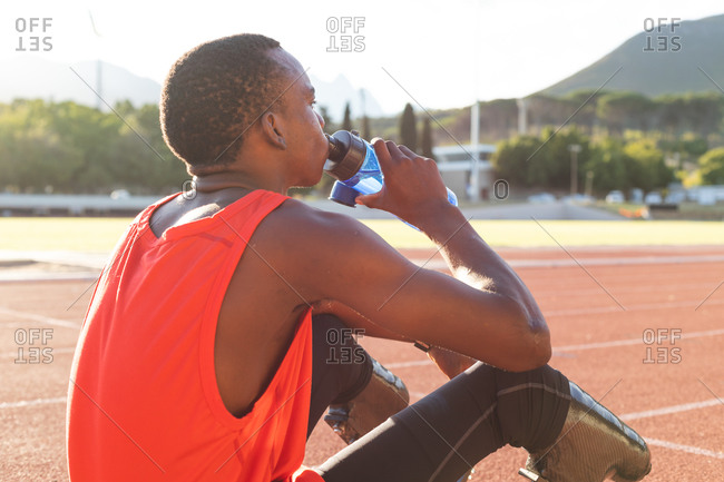Fit, mixed race disabled male athlete at an outdoor sports stadium, resting and drinking from water bottle on race track wearing running blades. Disability athletics sport training.