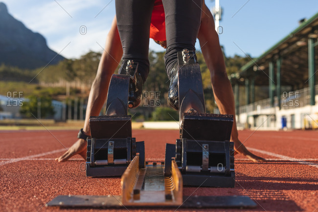 Fit, mixed race disabled male athlete at an outdoor sports stadium, bending in starting blocks on race track wearing running blades. Disability athletics sport training.