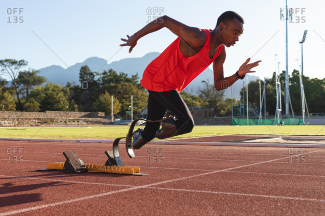 Fit, mixed race disabled male athlete at an outdoor sports stadium, starting sprint from starting blocks on race track wearing running blades. Disability athletics sport training.