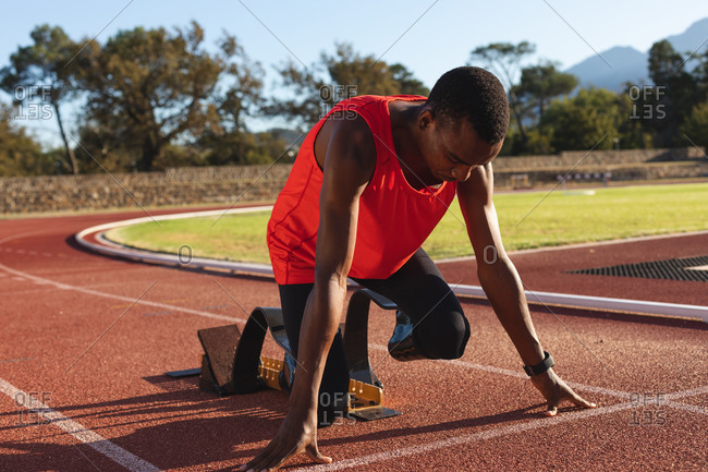 Fit, mixed race disabled male athlete at an outdoor sports stadium, kneeling in  starting blocks on race track wearing running blades. Disability athletics sport training.