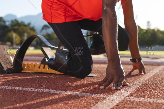 Low section of fit, mixed race disabled male athlete at an outdoor sports stadium, kneeling in starting blocks on race track wearing running blades. Disability athletics sport training.